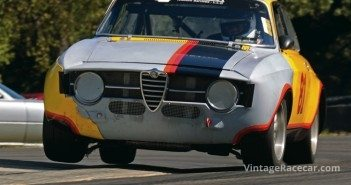 Rob Mocas hops a wheel over the curbs at the Oak Tree turn in his 1967 Alfa Romeo GTV.