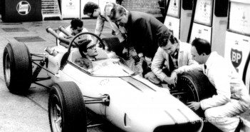 Masten Gregory sits in the cockpit of the 1965 BRP Indycar as team manager Tony Robinson looks on.