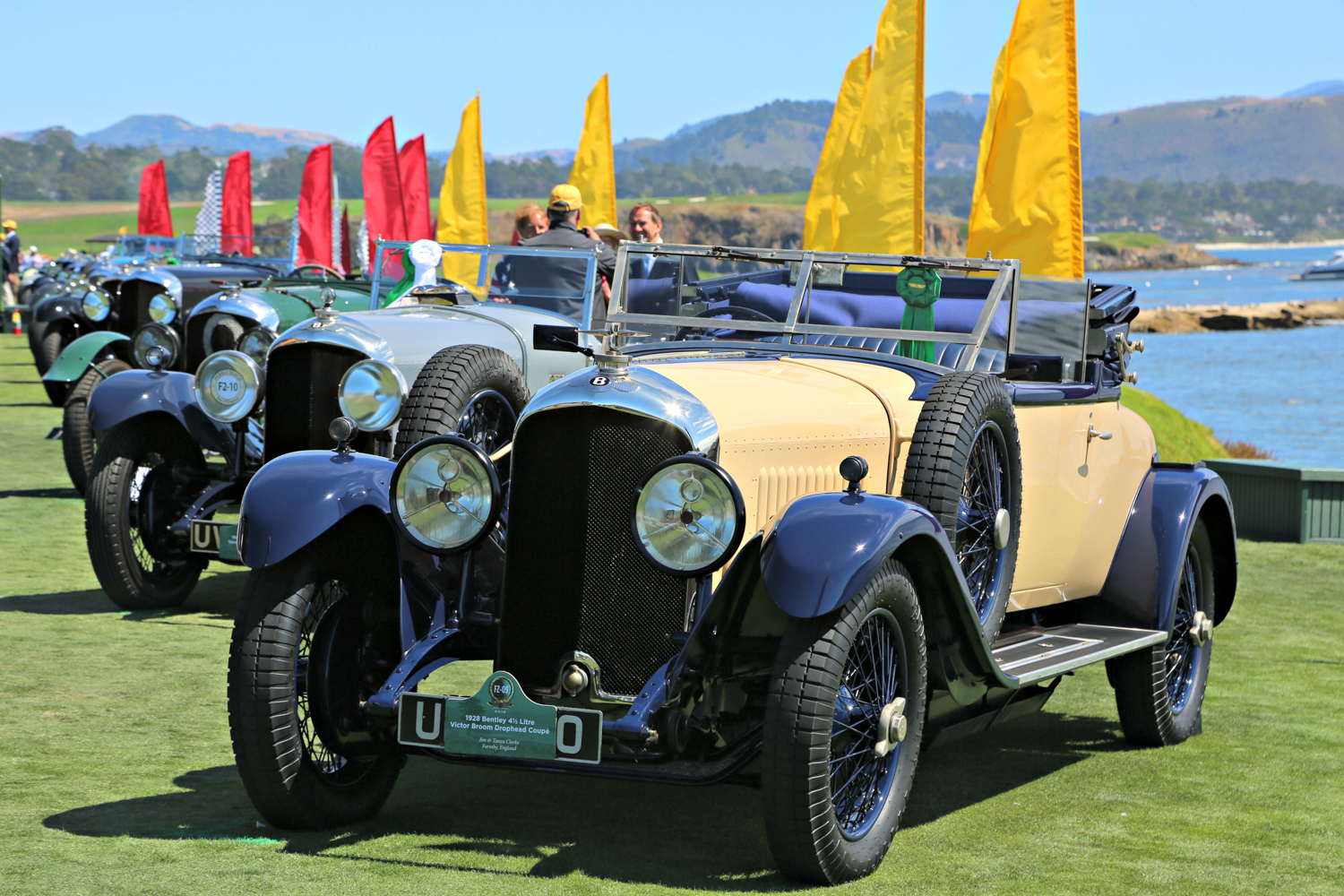 A 1928 Bentley 4 1/4 Litre Victor Broom Crophead Coupe owned by Jim & Tanya Clarke leads an impressive line of Bentley automobiles to celebrate the 100th anniversary of the marque.